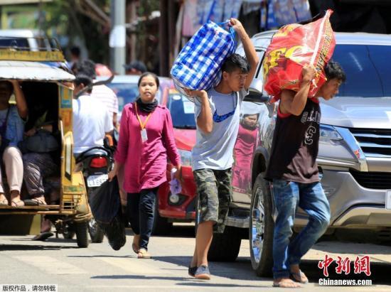 马拉维自5月23日爆发反恐战事,战斗一直持续至今。10月17日,随着两名恐怖分子头目被击毙,菲律宾总统杜特尔特亲赴前线,宣布马拉维市获得解放。图为马拉维民众从临时安置点撤离,打包回家。
