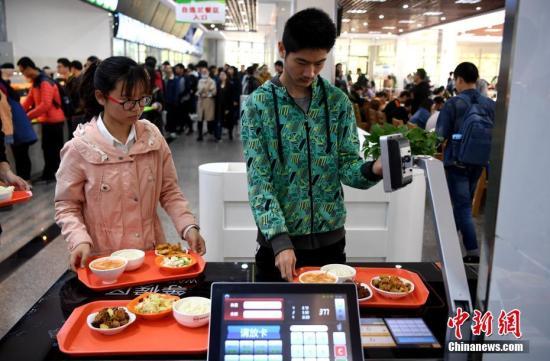 学生将打好的饭菜放在智能结算台上进行结账。中新社记者 韩苏原 摄