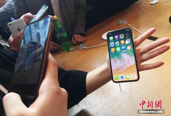资料图:在上海南京东路的一家苹果直营店内,民众在拍摄iphoneX手机殷立勤 摄