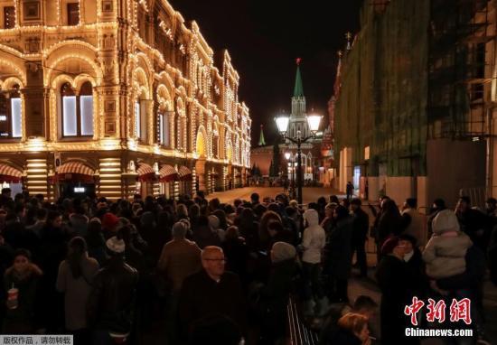 """俄安全局局长博尔特尼科夫说,目前已证实这些匿名炸弹威胁电话的主谋是4名身处他国的俄罗斯人。这4人可能与""""伊斯兰国""""恐怖组织有联系。俄已对4人展开全球通缉。图为""""古姆""""商场外,警察封锁了道路,人们排队等待。"""
