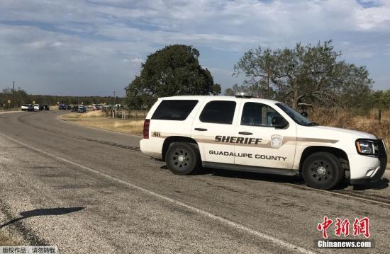 图为得州当地警方的车辆停靠在枪击事故现场附近。