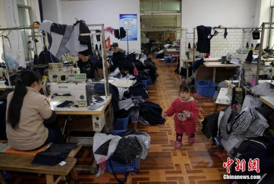 资料图:成都郫都区安靖镇土地村某服装加工厂车间内一小女孩正在玩耍,其母亲正坐在缝纫机前赶制服装。