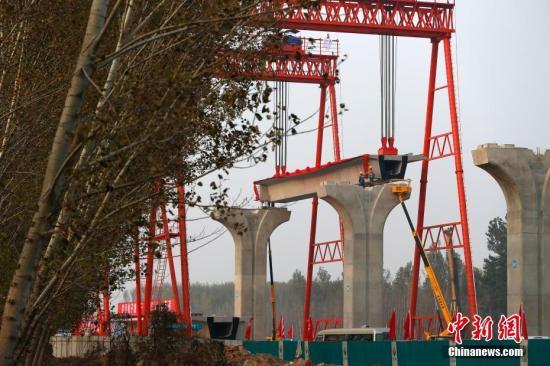 11月6日,北京轨道交通新机场线第一片梁,在大兴区礼贤镇的新机场线土建施工一期工程02标工地开始架设。据悉,架设预计2018年6月30日结束,线路则于2019年与新机场同时运行。北京新机场轨道线设计时速每小时160公里,是目前内地最快的城市轨道交通工程。途经大兴、丰台两个行政区,线路全长41.36km,包括盾构段、高架段,设新机场北航站楼站、磁各庄、草桥三座车站。中新社记者 富田 摄