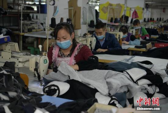 资料图:成都郫都区安靖镇土地村某服装加工厂内工人师傅们加班加点赶制服装。