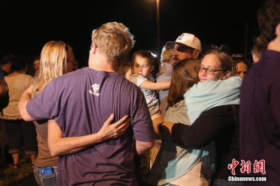 资料图:当地时间11月5日,美国得克萨斯州南部小镇萨瑟兰斯普林斯(Sutherland Springs)一处教堂发生枪击事件,共造成26人死亡。图为枪击案发生当晚,百余民众聚集在镇邮局门口进行守夜活动,悼念遇难者。 <a target='_blank' href='http://www.chinanews.com/'>中新社</a>记者 曾静宁 摄