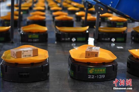 """资料图:11月9日,智能分拣机器人""""小黄人""""在安徽邮政合肥邮区中心局正式上岗。图/韩苏原"""