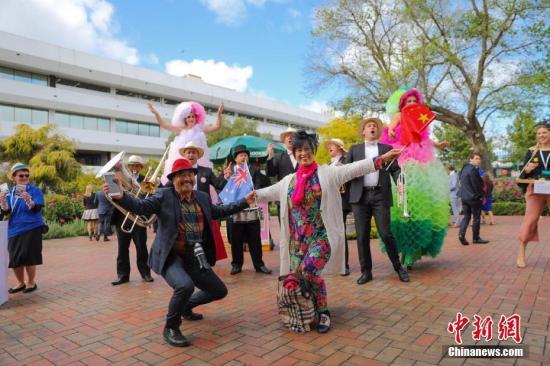 """资料图片:全球闻名的""""墨尔本赛马节""""吸引不少中国游客。图为一对来自中国的夫妇伴着乐队的音乐和歌声,挥舞着中澳两国国旗翩翩起舞。<a target='_blank' >中新社</a>记者 陶社兰 摄"""