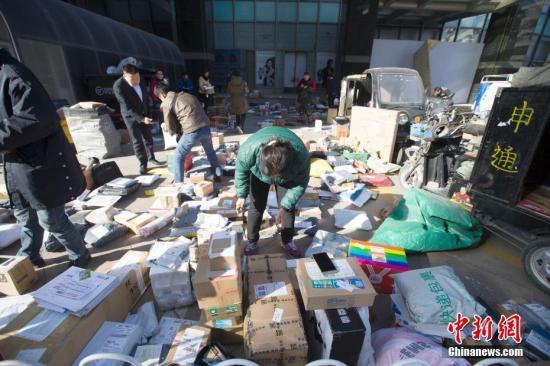 """资料图:随着""""双十一""""网购落下帷幕,中国物流业迎来派送快递高峰。11月13日,山西太原,物流工作人员正在分拣快递。 张云 摄"""