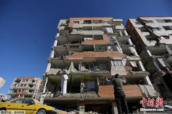 当地时间11月12日晚间发生在伊朗和伊拉克边界地区的7级以上强震,已造成至少348人遇难,超过5000多人受伤,70000人因地震无家可归。据悉,此次强震后,大约发生了50次余震。地震在伊朗多地引起恐慌,居民连夜跑到街上避难,围着篝火在户外过夜。与此同时,伊朗当局也向受灾地区提供援助。伊朗救援人员13日继续在废墟中搜寻幸存者。不过,地震还引发山体滑坡,影响救援人员接近灾区。图为伊朗克尔曼沙赫县的一栋建筑严重损毁。