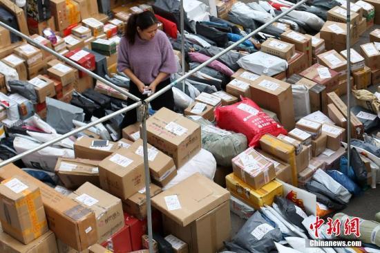 """11月14日,南京一高校校园内,大学生在快递点领取各自的快件。网络购物""""双十一""""过后,各地迎来快件派送高峰。 <a target='_blank' href='http://www.chinanews.com/'>中新社</a>记者 泱波 摄"""
