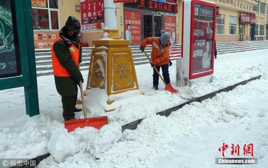 11月14日,内蒙古呼伦贝尔市牙克石街头,环卫工在清理积雪。余昌军 摄 图片来源:视觉中国