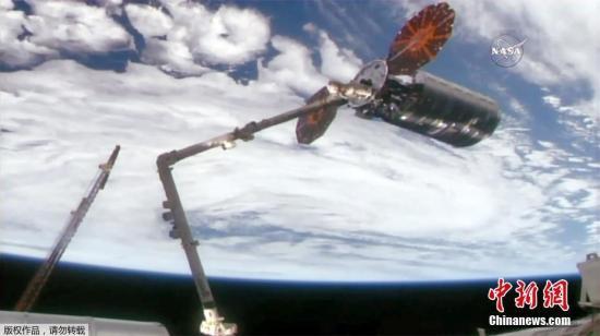 """资料图:2017年11月15日讯,美国宇航局发布的图片显示14日国际空间站的加拿大臂2号抓住""""天鹅座""""飞船。"""