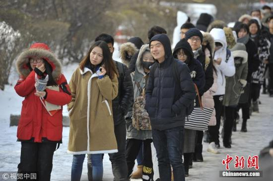 2017年11月15日,哈尔滨市某高校,寒冷的冬天大学生们雪地中排队领取双十一快递。 图片来源:视觉中国