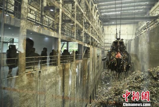 资料图:民众在重庆垃圾焚烧厂参观堆积成山的垃圾。 陈超 摄