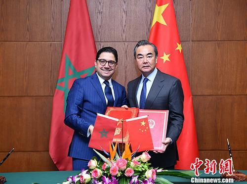 """11月17日,中国外交部部长王毅(右)在北京与来访的摩洛哥外交与国际合作大臣布里达签署《中摩两国政府关于推进""""一带一路""""建设的谅解备忘录》。 中新社记者 侯宇 摄"""