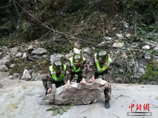 图为部队官兵清理道路巨石。武警交通部队供图