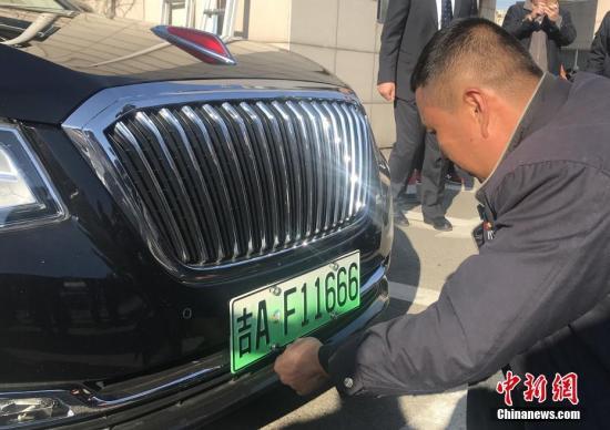 长春市民为爱车安装新能源汽车专用号牌。 中新社记者 张瑶 摄