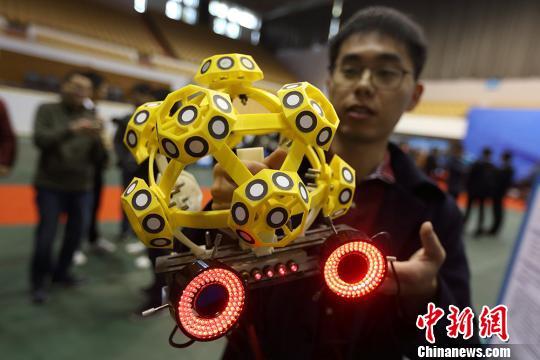 """资料图:大学生展示他参与设计的""""机器人装配式光学三坐标3D测量仪""""。 泱波 摄"""