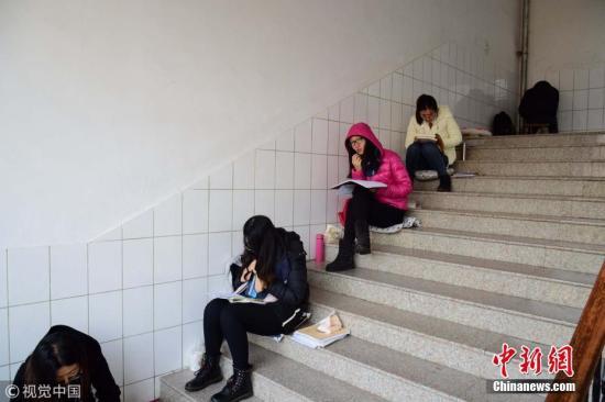 图为考研生在楼道内背诵考试内容。小老茂 摄 图片来源:视觉中国