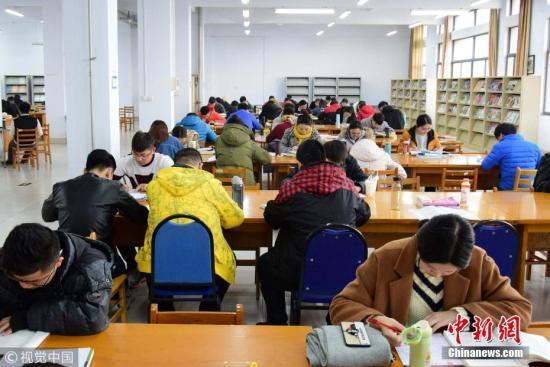 资料图:考研倒计时,青岛高校考研族做最后冲刺。图为考研生在图书馆内埋身书海认真复习。小老茂 摄 图片来源:视觉中国