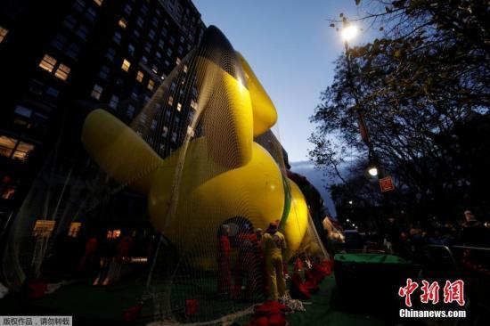 当地时间2017年11月22日,美国纽约,一年一度的梅西感恩节大游行即将举行,工作人员正在进行准备工作,民众在街边围观。