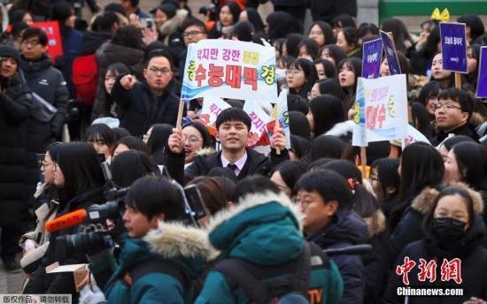 11月23日,在韩国首尔,因地震推迟举行的高考当日举行,学弟学妹为参加高考的考生加油助威。