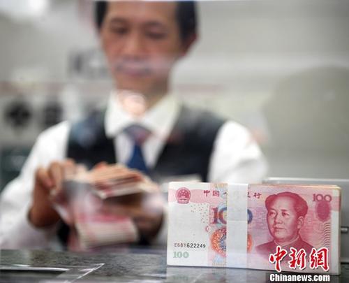 11月23日,中国外汇交易中心发布数据,人民币对美元汇率中间价报6.6021,较前一交易日大幅上涨269个基点。图为广西南宁一银行工作人员清点货币。(资料图片)记者 俞靖 摄