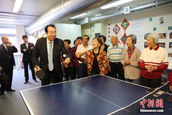 11月25日,中国国务院侨务办公室党组书记、副主任许又声走访新西兰侨界。图为许又声在奥克兰华人社区服务中心与侨胞打乒乓球。记者 陶社兰 摄