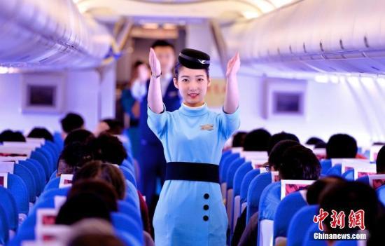 """11月25日,经过3个月的初始培训,厦门航空首批台湾籍乘务员正式开始上机飞行。这不仅标志""""厦航台籍青年就业千人计划""""稳健走出第一步,更标志""""台湾青年就业创业基地""""首批学员正式步入工作岗位。图为首次上机飞行的台湾级空姐刘舒亚在航班上为旅客演示安全须知。贺晟 摄"""