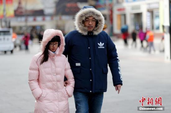 """资料图:大风降温,民众全副""""武""""装防寒出行。 中新社记者 杜洋 摄"""