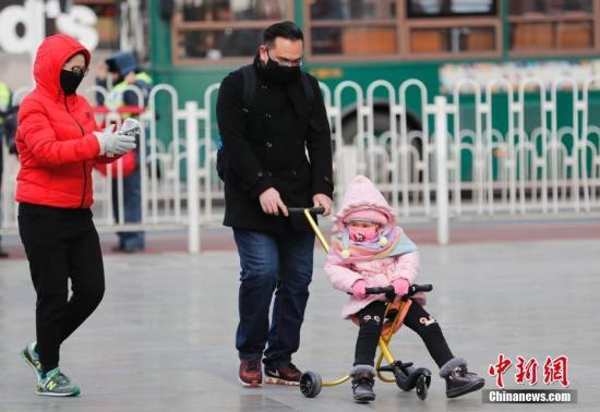 """11月29日,受冷空气影响,北京急速降温,民众全副""""武""""装防寒出行。 中新社记者 杜洋 摄"""