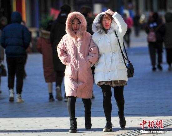 11月29日,辽宁沈阳,市民穿着冬装出行。当日,受冷空气影响,沈阳最高气温为-5℃,最低温仅为-14℃。 中新社记者 于海洋 摄