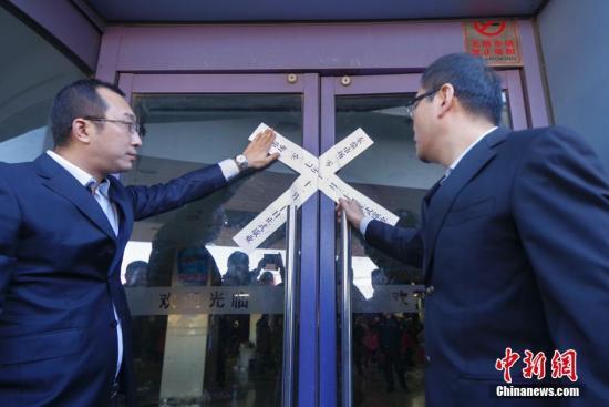 """资料图:北京""""动批""""东鼎服装批发市场正式关闭,工作人员在门口贴上封条。 <a target='_blank' href='http://www.chinanews.com/'>中新社</a>记者 贾天勇 摄"""