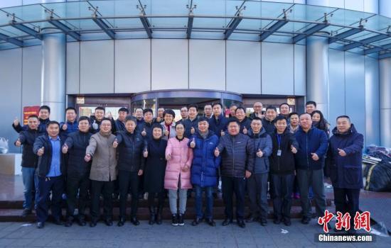 """资料图:北京""""动批""""东鼎服装批发市场正式关闭,市场管理人员在门前合影留念。 <a target='_blank' href='http://www.chinanews.com/'>中新社</a>记者 贾天勇 摄"""
