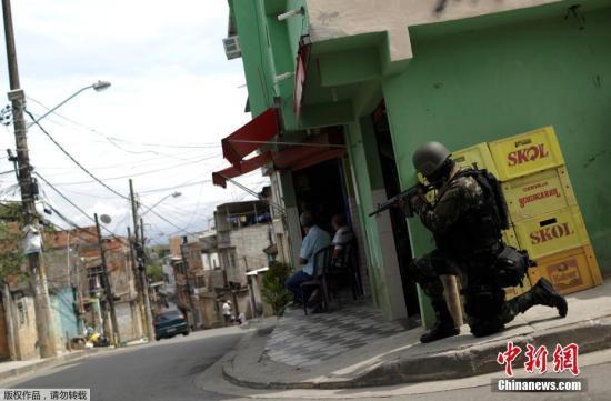 资料图:当地时间2017年11月30日,巴西士兵在里约热内卢Barbante贫民窟巡逻。警方在打击毒贩行动中与犯罪分子发生激烈交火,警察局遭破坏。