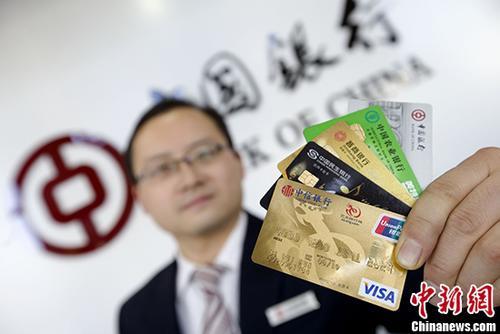 资料图:银行工作人员展示各类信用卡。 <a target='_blank' href='http://www.chinanews.com/'>中新社</a>记者 张云 摄