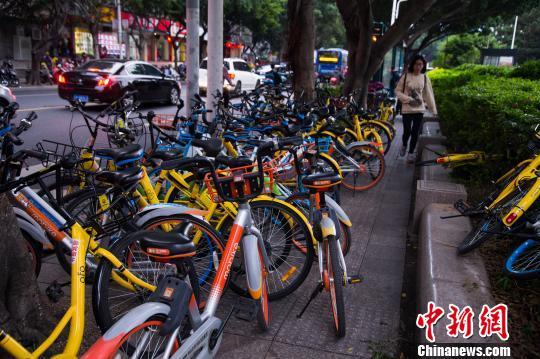 共享单车占用人行道,行人通过艰难。 李南轩 摄