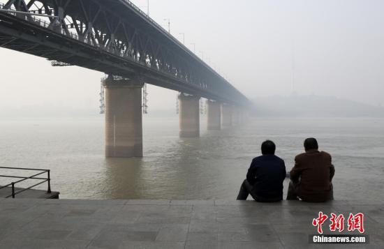 12月4日,武汉长江大桥笼罩在霾中。当日,武汉市发布霾黄色预警,空气质量指数达到275为重度污染级别。中新社记者 张畅 摄