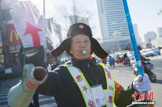 """12月5日是国际志愿者日,在寒风凛冽的山西太原街头,77岁的志愿者马金明步履蹒跚地走在五一广场指挥交通。1974年,在国营饭店当服务员的马金明因工伤致下半身瘫痪,热衷公益的他却靠着坚强的信念,在21年后奇迹般地站了起来。从2010年开始,无论是寒酷节假,马金明都在这里义务疏导交通。""""我跟雷锋同岁,一辈子就学他为人民服务。""""马金明说。中新社记者 韦亮 摄"""