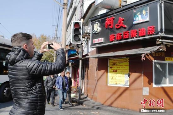 """12月5日,位于上海霍山路203号的阿文夜市豆浆油条店已经歇业。这个北外滩地区十分有名的网红油条店涉嫌无证经营,被相关区市场监管局予以取缔。12月4日,在上海消保委发布""""油条消费体察情况""""通报会上,报告了29家餐饮店的检测结果;上海市食药监表示,上述29家餐饮店中,有5家涉嫌无证,相关区市场监管局已会同当地政府和相关部门予以取缔。<a target='_blank' href='http://www.chinanews.com/'>中新社</a>记者 殷立勤 摄"""