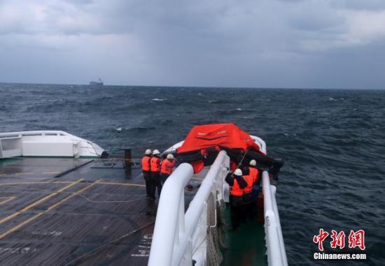 """12月4日9时许,纽埃籍船舶""""SHENGHAI""""号由韩国釜山开往烟台途中,经过威海成山头以东海域时遭遇大风浪,船舶摇晃剧烈造成集装箱移位,船舶失去平衡引发侧翻,并沉没。船上10名缅甸籍船员全部落水,经各方全力搜救,先后发现并成功救起7名船员,其他3人目前暂无消息。图为北海救助局搜救人员商讨救援方案。 刘飞 摄"""