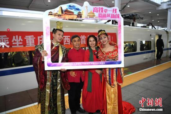 图为发车前动车组工作人员穿着古装与旅客合影留念。 中新社记者 陈超 摄