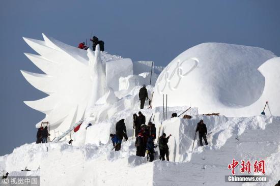 """12月6日,第30届哈尔滨太阳岛国际雪雕艺术博览会大型主雪塑《雪颂冬奥》正加紧雕刻。这座主雪雕有3个突出特点,近300米的总长度创雪博会历史之最;高达35米的主塑""""飞翔""""人体,突破历届雪博会主塑人体高度;雪博会大型雪滑梯与主塑相连接,让游客能在参与打雪滑梯的同时,可以登上雪博会主雪塑之上,亲身体验巨大雪塑群的艺术美感和震撼效果。 小刘 摄 图片来源:视觉中国"""