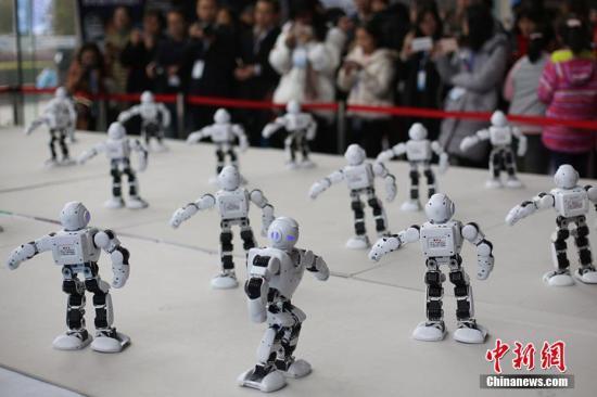 """12月6日,""""机器人""""集体舞吸引了参观者的目光。当日,2017世界智能制造大会在南京召开,来自全球的顶尖专家、行业领军人物齐聚一堂,围绕""""聚・融・创・变""""主题,共同描绘清晰美好的智造未来。大会同时举办全球博览会,智能家居、未来机器人、智慧医疗等国内外智能制造领域的最新技术和顶尖产品缤纷亮相。泱波 摄"""