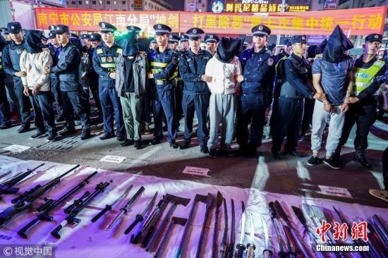 资料图:2017年12月4日至5日,南宁抓获涉黑涉恶犯罪嫌疑人 地上摆满枪支刀具。