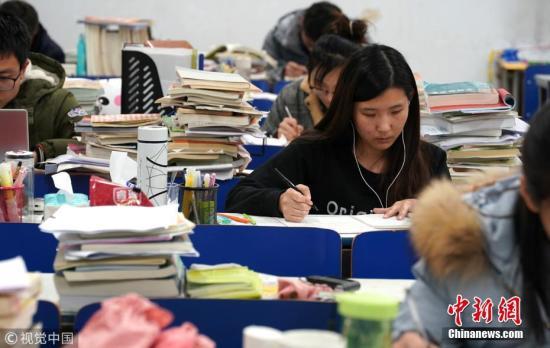 """探访高校""""考研族""""。图为课桌上,堆满复习资料。马健 摄 图片来源:视觉中国"""