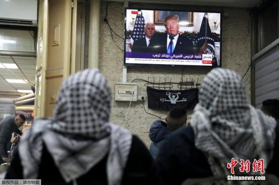 资料图:巴勒斯坦民众在耶路撒冷旧城区观看特朗普发表公告的直播画面。