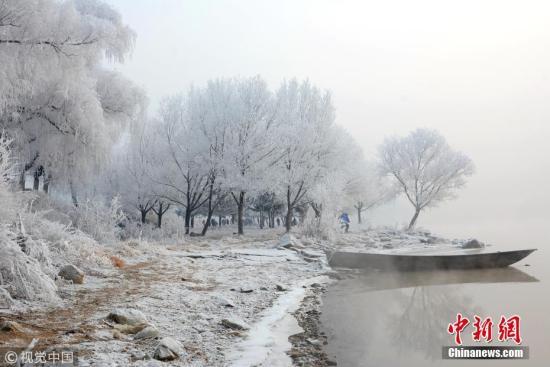 12月7日,游客们在吉林省吉林市小雾凇岛上观赏拍摄迷人的雾凇美景。当日,吉林市最低温度下降到零下21度,松花江畔雾气缭绕,呈现出雾凇景观,吸引了众多外地游客纷纷前来观赏拍照。 王明铭 摄 图片来源:视觉中国