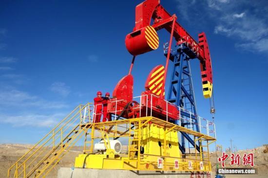 资料图:青海尕斯油田,采油技师检查抽油机。中新社记者 孙睿 摄