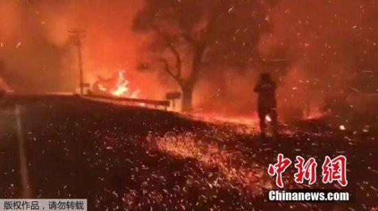 山火借助风力迅速蔓延,图为加州一公路上火星四溅。(视频截图)